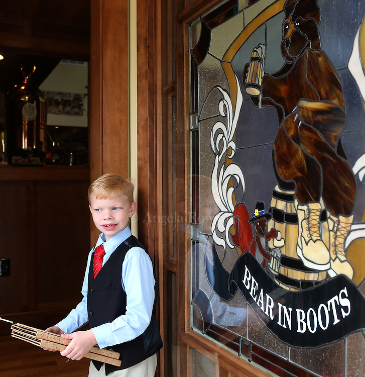 (Falmouth, MA - 5/28/15) Charlie Rickard, 8, works weekends as a maitre d' in his parents' Falmouth restaurant, Bear in Boots, Thursday, May 28, 2015. He says he is better on the computer than his mom, so he is able to update the tables quickly, and he enjoys talking with people. Staff photo by Angela Rowlings.