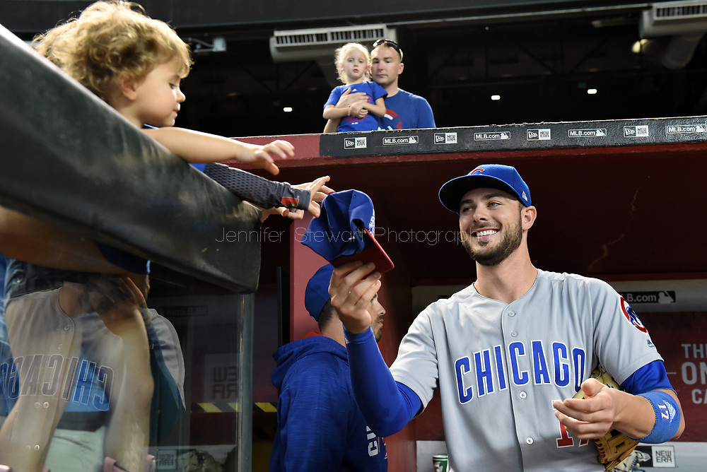 Aug 12, 2017; Phoenix, AZ, USA; Chicago Cubs infielder Kris Bryant (17) smiles while signing an autograph for a young fan prior to the MLB game between the Chicago Cubs and Arizona Diamondbacks at Chase Field. Mandatory Credit: Jennifer Stewart-USA TODAY Sports