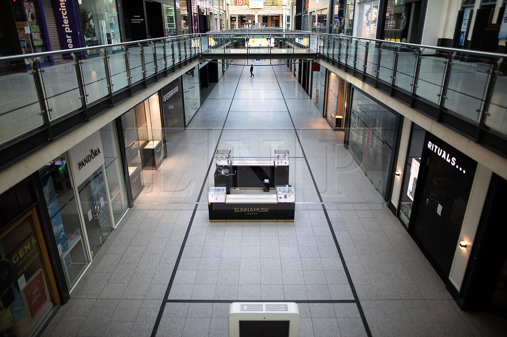 © Licensed to London News Pictures. 26/03/2020. Manchester, UK. A single person can be seen inside The Arndale Centre . Manchester City Centre lies nearly empty during a sunny spring afternoon . The British government has imposed a lockdown on all but essential activities and instructed people to reduce social contact as part of quarantine measures to prevent the spread of Coronavirus ( COVID-19 ) . Photo credit: Joel Goodman/LNP