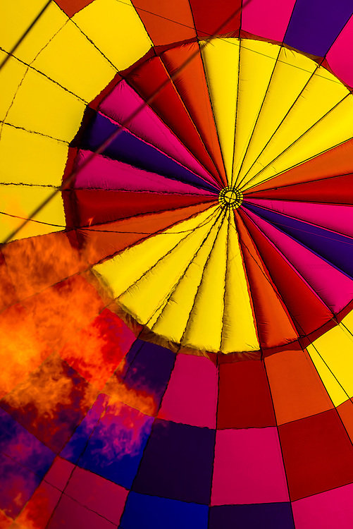 Flame from the burner against the colorful hot air balloon envelope (balloon is named Sunglow) as it was being inflated, Albuquerque International Balloon Fiesta, Albuquerque, New Mexico USA.