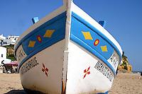 Fishing boat on beach, blue sky overhead, Algarve Portugal