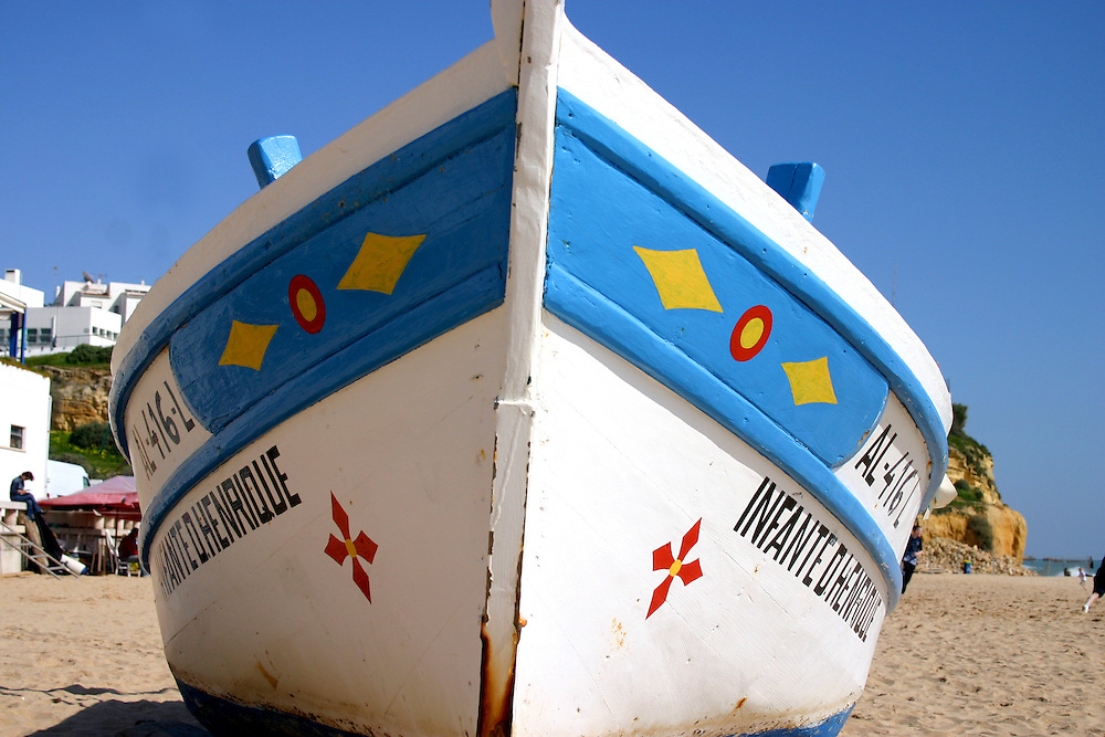 Fishing boat on beach, blue sky overhead, Algarve Portugal