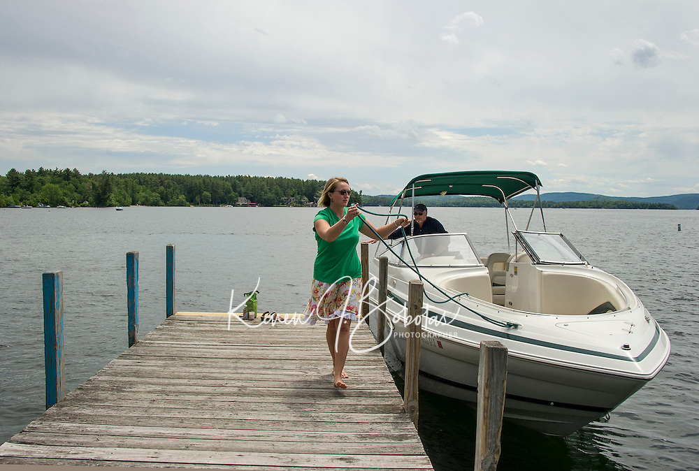 Hannah Seibel helps Rick Murray with his lines as he pulls up to the town docks in Wolfeboro, NH.    ©2106 Karen Bobotas Photographer