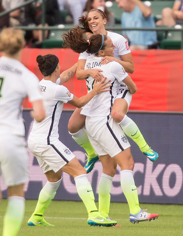 The United States' Alex Morgan (top) is lifted by teammate Lauren Holiday as they celebrates her goal during their FIFA Women's World Cup Group of 16 Match against Colombia at Commonwealth Stadium in Edmonton, Canada on June 22, 2015.   AFP PHOTO/GEOFF ROBINS