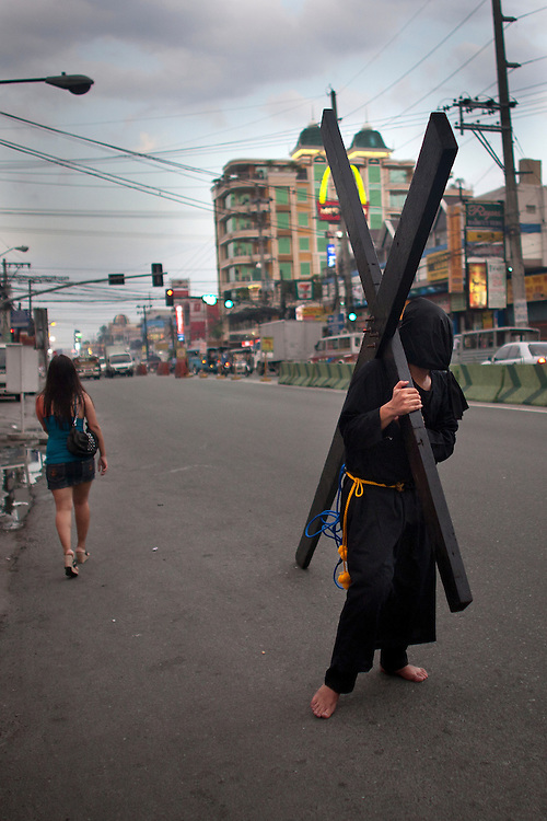 A hooded penitent carrying his cross through village streets to atone for their sins in observance of Holy Week, Thursday, April 5, 2012 at Los Angeles city, Philippines.