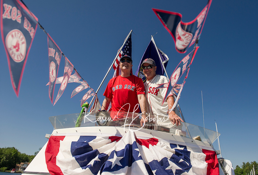 Captain Steve Nix and his First Mate Hayden McLaughlin on board the SS Minnow decked out for the Boston Red Sox navigate their way to the Winnipesaukee Yacht Club's 4th of July boat parade on Monday morning.  (Karen Bobotas/for the Laconia Daily Sun)