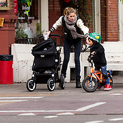 NLD/Amsterdam/20141221- Victoria Angel Doutzen Kroes wandelend met dochter Myllena Mae in de kinderenwagen en zoon Phyllon op zijn fiets.<br /> .<br /> .<br /> Victoria Angel Doutzen Kroes walking with her daughter Mae Myllena in the stroller and son Phyllon on his bike