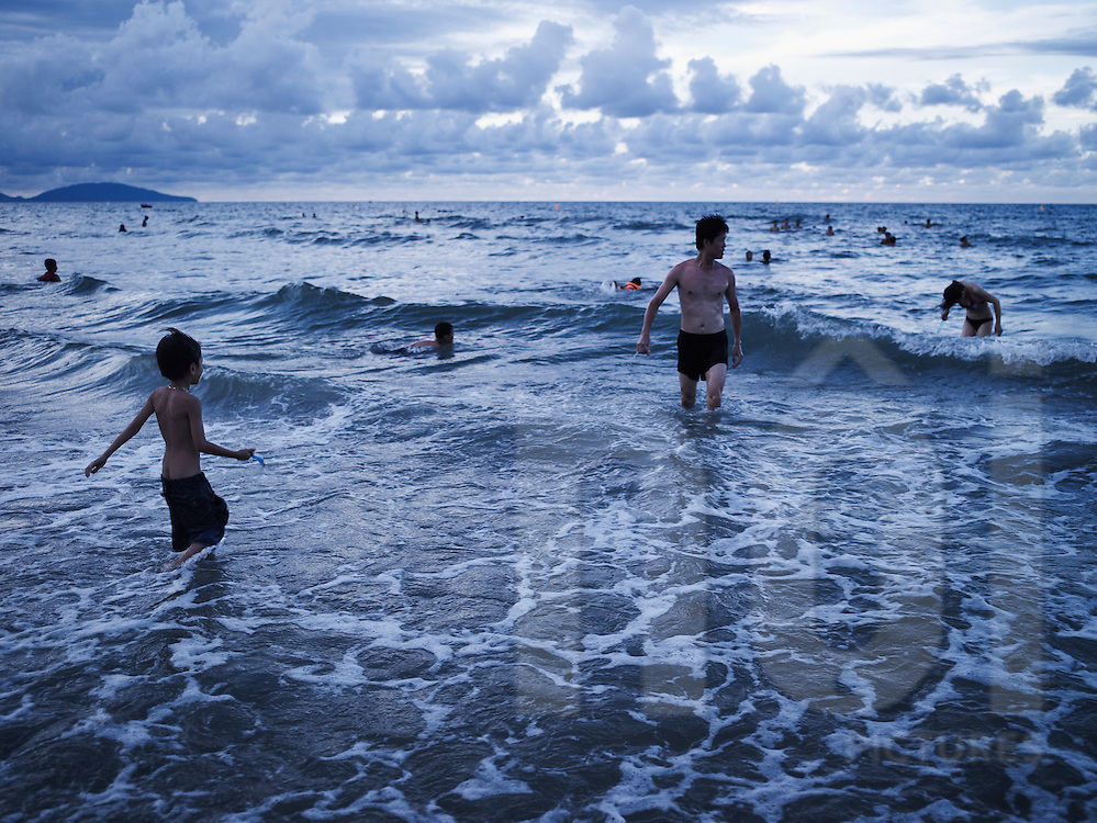 A vietnamese family bath along a shore in Hoi An, Vietnam, Asia