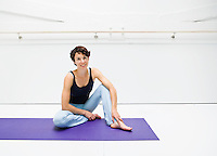 A portrait of a smiling woman sitting in a white room on a yoga mat.