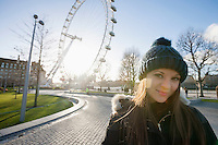 Portrait of beautiful young woman in front of London Eye; London; UK
