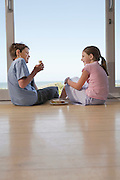 Young girl and boy sitting on floor in doorway eating sandwiches