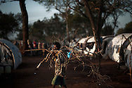 A man displaced by the war between the government of Sri Lanka and the LTTE carries fire wood in a camp for internally displaced people at the Menick farm near Vavuniya, Sri Lanka on July 8, 2009. Nearly 300,000 people remain in camps after the war as the government works on resettling them and screening for remaining LTTE members.