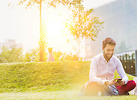 Portrait of young attractive businessman using smartphone while sitting on the grass