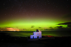 © Licensed to London News Pictures. 06/03/2016. Bamburgh, UK. Aurora borealis seen vividly over a lighthouse on the north east coast at Bamburgh, Northumberland, Uk on March 06, 2016. Known as the 'northern lights' the polar light creates a spectacular show of bright colours in the sky. Photo credit: Mark Hume/LNP