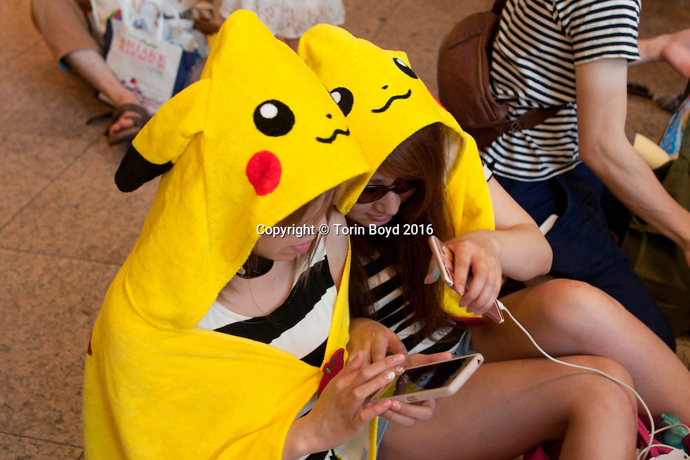 August 7, 2016, Yokohama, Japan: These are fans at Pikachu Outbreak!, a weeklong extravaganza dedicated to Pikachu, the lovable Pokemon character held in Yokohama from August 7 -14, 2016. This annual summer event started in 2014 involves hundreds of Pikachu mascots and huge inflatables making appearances at venues throughout the city's waterfront district known as Minato Mirai. Events include a parade of dancing Pikachu mascots, a large gathering of Pikachu splashing themselves and fans, a hula dance event, a Pikachu fishing pool, stage performances, Pikachu merchandise for sale and Pikachu photo studios. (Torin Boyd/Polaris).