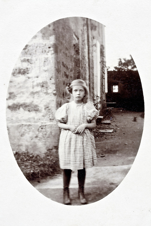 young girl posing at the corner of the house early 1900s France