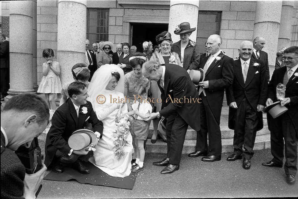 05/07/1967<br /> 07/05/1967<br /> 05 July 1967<br /> Wedding of George Walsh, eldest son of Mr and Ms Kevin G. Walsh, St. Rita's, Firhouse Road, Templeogue, Co. Dublin and Miss Arlene McMahon, elder daughter of Det. Chief Supt. Philip McMahon, Head of Special Branch, Dublin Castle and Mrs McMahon of Lisieux, Templeville Park, Templeogue, Co. Dublin who were married at the Carmelite Church, Terenure College, Dublin. An Taoiseach Mr Jack Lynch and Mrs Lynch; Mr Liam Cosgrave, leader Fine Gael and Mrs Cosgrave were among the 120 guests. Rev Fr H.E. Wright, O. Carm., Moate, officiated at the ceremony. The reception was held at Downshire Hotel, Blessington, Co. Wicklow. Image shows Mr Jack Lynch and a page boy congratulate the couple outside the church after the ceremony.