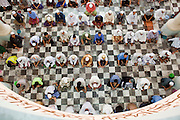 "Sept. 25, 2009 -- PATTANI, THAILAND: Men gather for Friday prayers in the Central Mosque in Pattani, Thailand. The mosque's Imam said a special prayer on this day for the Thai King who is in a hospital in Bangkok. Pattani's Central Mosque is considered the most architecturally striking mosque in Thailand and was a leading tourist site until the current violence put an end to mass tourism in Pattani. Thailand's three southern most provinces; Yala, Pattani and Narathiwat are often called ""restive"" and a decades long Muslim insurgency has gained traction recently. Nearly 4,000 people have been killed since 2004. The three southern provinces are under emergency control and there are more than 60,000 Thai military, police and paramilitary militia forces trying to keep the peace battling insurgents who favor car bombs and assassination.  Photo by Jack Kurtz"