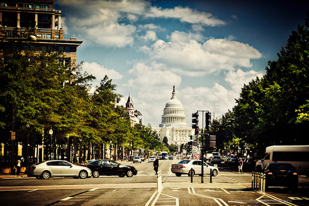A busy street in Washington DC with the Capitol building in the distance (Image contans some grain)
