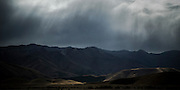 A small pocket of light graces the hillside, amongst the shadows of a rain storm over the mountain range behind Twizel.  As the storm progressed, the light danced off and on the dark valleys.