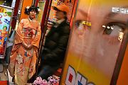 Entrance of patsinko parlour in Yurakucho. Patsinko employee dressed in a kimono welcomes customers.