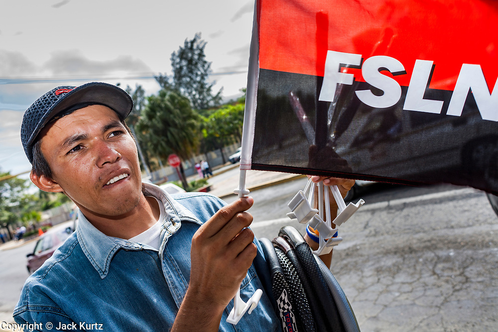 """10 JANUARY 2007 - MANAGUA, NICARAGUA:  A man sells Sandanista (FSLN) flags and bicycle tires on a street corner in Managua, Nicaragua. Daniel Ortega, the leader of the Sandanista Front, was sworn in as the President of Nicaragua Wednesday. Ortega and the Sandanistas ruled Nicaragua from their victory of """"Tacho"""" Somoza in 1979 until their defeat by Violetta Chamorro in the 1990 election.  Photo by Jack Kurtz"""