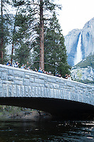 Image of photographers on bridge taking photos of Half Dome with Yosemite Falls in the background. Yosemite National Park, CA.