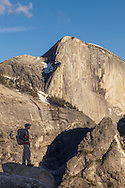 A backpacker stands on an outcropping admiring the view while Half Dome rises high overhead, Yosemite National Park