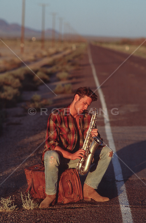 man on the side of a road playing a saxophone