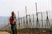 "A security man who does not want to be identified by name guards with a Uzi sub machine gun   early morning Friday November 22,2002 by the electric barbed wire fence along the village Israeli Arab village of Salem near the West Bank city of Jenin . The guard say's that it is either ""them or us""Aprox. 1.5 kilometers of barbed wire fence has been erected so far.The fence Israel claims will prevent Palestinian suicide bombers will run along the West Bank. The barrier is expected to eventually run the full length of the 300-kilometer (180-mile) frontier between Israel and the West Bank, which it occupied in the 1967 Mideast war.(Photo by Heidi Levine/Sipa Press)."