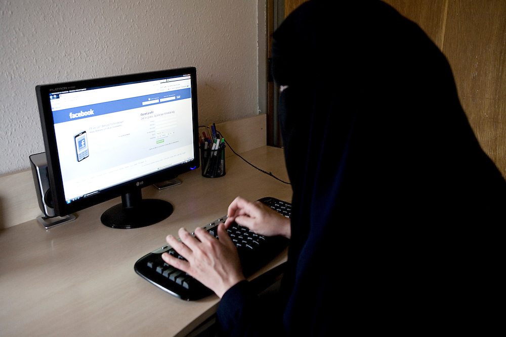 "Arhus, Denmark, May 13, 2010. Aisha, 42, danish, converted to Islam. Aisha explains that the picture of a woman wearing a niqab on her face-book profile is not her, ""but no one will notice,"" she says laughing."