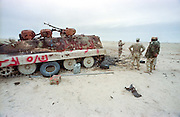 Qatar soldiers examine destroyed Iraqi armored personnel carriers destroyed by U.S Forces during the Battle of Khafji February 2, 1991 in Khafji City, Saudi Arabia. The Battle of Khafji was the first major ground engagement of the Gulf War.