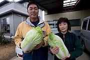 Mitsuo Sugawara and his wife Tomoko pose with Sendai Hakusai cabbages grown on their farm in Higashi-Matsushima, Miyagi Prefecture, Japan n 30 Nov. 2011.Photographer: Robert Gilhooly