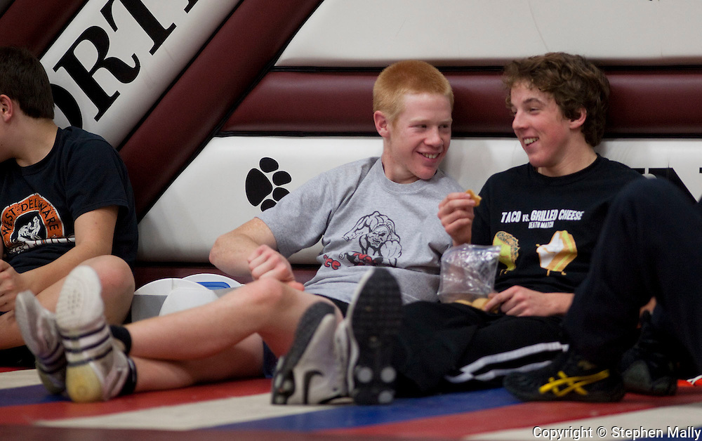 West Delaware's Matt Marbach (from left), 16,  talks with teammate Reilly Ryan as they eat before the start of the varsity round at North-Linn Community School at 3033 Lynx Drive in Troy Mills on Saturday morning, December 18, 2010.
