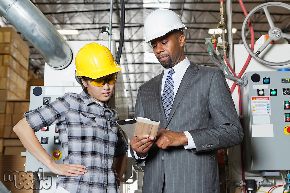 Female industrial worker and male engineer in discussion at timber factory