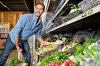 Happy young man shopping for vegetables in market