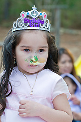 young latin girl wearing a princess birthday tiara, with icing on her face