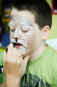 Boy of 8 being made up as tiger