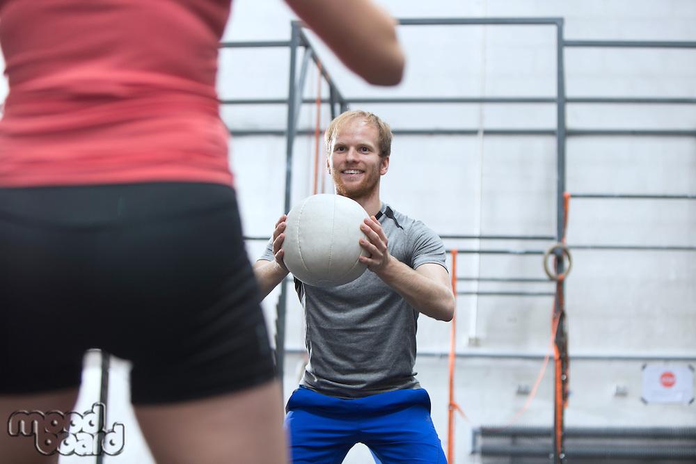 Happy man throwing medicine ball towards woman in crossfit gym