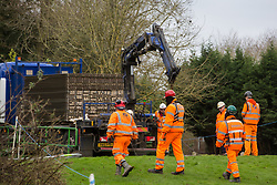 Denham, UK. 4 February, 2020. Engineers and security guards walk across land cleared for works for the HS2 high-speed rail link project. Behind other engineers prepare to unload a temporary roadway from a large truck. Planned works in the immediate vicinity are believed to include the felling of 200 trees and the construction of a roadway, Bailey bridge, compounds, fencing and a parking area. Credit: Mark Kerrison/Alamy Live News