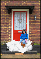 Albie Sean Underwood-White age 4 protect his sandbags from looters outside his home in Egham, United Kingdom, as the floods start to rise in the town, Wednesday, 12th February 2014. Picture by Andrew Parsons / i-Images