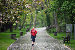 © Licensed to London News Pictures. 30/04/2018. London, UK. A woman jogs through a rain covered Holland Park in West London as parts of the UK are expected to experience an average months rain in 24 hours. Photo credit: Ben Cawthra/LNP