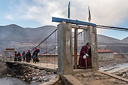 Citizens of Payul cross a bridge in the early morning. Amdo region, Tibet (Qinghai, China).