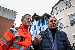 "© Licensed to London News Pictures. 16/11/2019. Bolton, UK. Assistant County Fire Officer DAVE KEELAN and President and Vice Chancellor of the University of Bolton PROFESSOR GEORGE HOLMES at a press conference at the scene as firefighters work after a fire broke out overnight (15th/16th November 2019) at a block of flats known as "" The Cube "" , in Bolton Town Centre . At least two people are known to have been treated by paramedics at the scene of the six-story block , which is occupied by students of the University of Bolton . Photo credit: Joel Goodman/LNP"