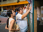 07 AUGUST 2016 - BANGKOK, THAILAND: An election worker (right) helps a woman (left) look for her name on voting rolls at a polling place at Wat That Thong in Bangkok. Thais voted Sunday in the referendum to approve a new charter (constitution) for Thailand. The new charter was written by a government appointed panel after the military coup that deposed the elected civilian government in May, 2014. The charter referendum is the first country wide election since the coup.      PHOTO BY JACK KURTZ
