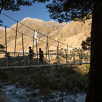 The beginning of the Rob Roy Glacier Track leads hikers over the Matukituki River via a swing bridge into a beech forest in the Matukituki Valley near Wanaka on the South Island of New Zealand.