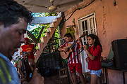 Aimar Romero, 15 plays the guitar as his sister Kelly, 14 sings in Guarani as their father Jose Maria, left  and friends gather to a party after a soccer match at the Chacarita slum  in Asuncion, Paraguay, Saturday, Dec. 16, 2017. Paraguay today is trying to promote a positive image of Guaraní language, the native oral language that survived centuries of subjugation rendering it as a second class idiom in the minds of many Paraguayans that associated it with poverty, rurality, ignorance and illiteracy. (Dado Galdieri for The New York Times)