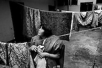 Maria del Carmen de Mata, 43, collects her laundry off the line in the courtyard of the Nuevos Horizantes shelter. de Mata, who was abandoned by her husband years ago, is a single mother of three children, two of whom live with her at the shelter. The eldest, Dalilia, 16, lives with her uncle.