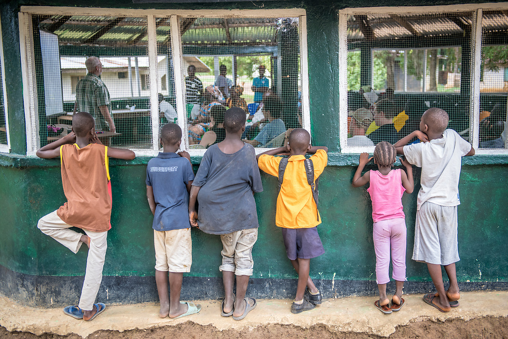 Kids peer through a window on a presentation in Ganta, Liberia