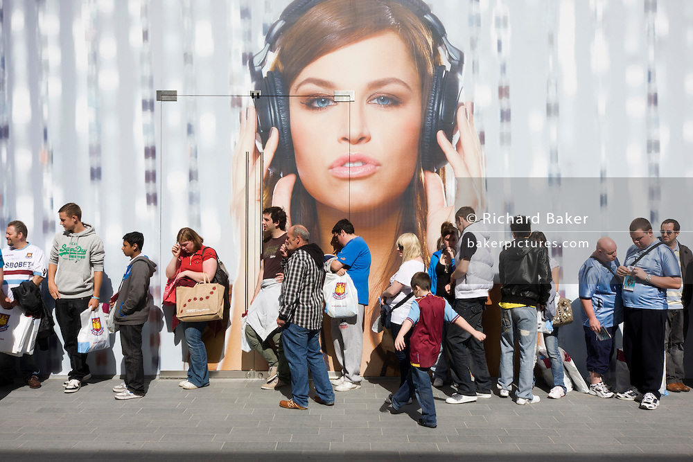 Londoners wait outside a soon to open shop for West Ham football merchandising on the opening day of the Westfield Stratford shopping mall. Situated on the fringe of the 2012 Olympic park, Westfield hosted its first day to thousands of shoppers eager to see Europe's largest urban shopping centre. The £1.45bn complex houses more than 300 shops, 70 restaurants, a 14-screen cinema, three hotels, a bowling alley and the UK's largest casino. It will provide the main access to the Olympic park for the 2012 Games and a central 'street' will give 75% of Olympic visitors access to the main stadium so retail space and so far 95% of the centre has been let. It is claimed that up to 8,500 permanent jobs will be created by the retail sector.